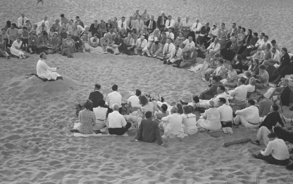 E Stanley Jones teaching in the sand on the beach by the sea